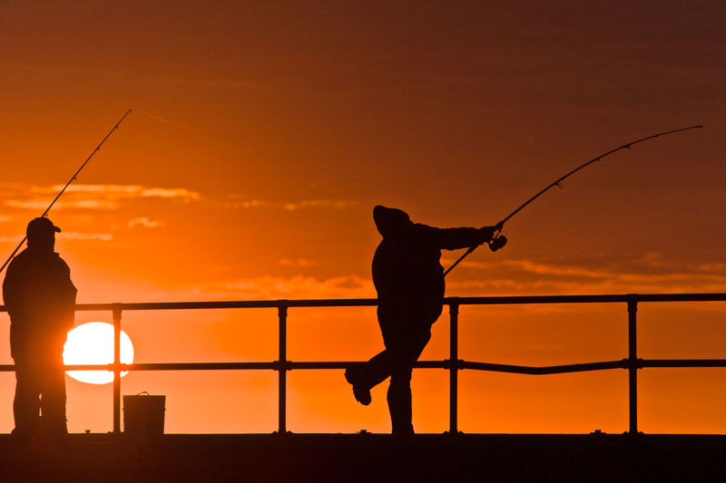 Silhouette Men Fishing By Railing Against Sky During Sunset