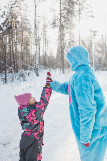 Father Wearing Costume Doing High-Five With Daughter On Snowy Field