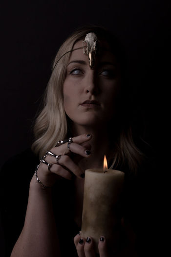 Portrait Of Spooky Woman Holding Lit Candle Against Black Background
