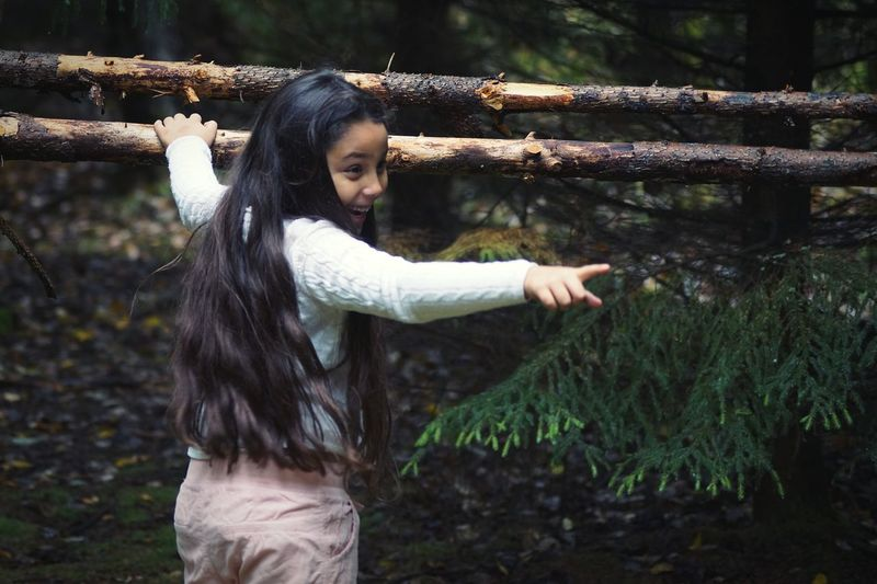 Rear View Of Girl With Long Hair Gesturing While Standing In Forest