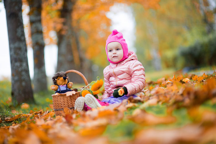 Cute baby girl sitting on field at park
