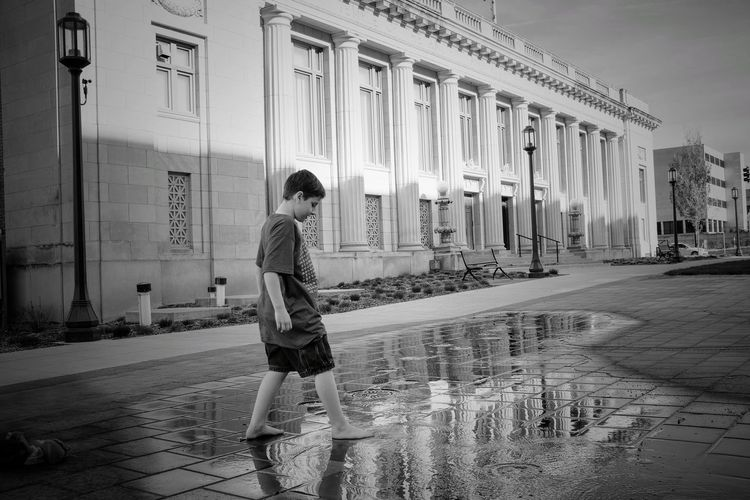 Boy standing against nebraska state capitol building