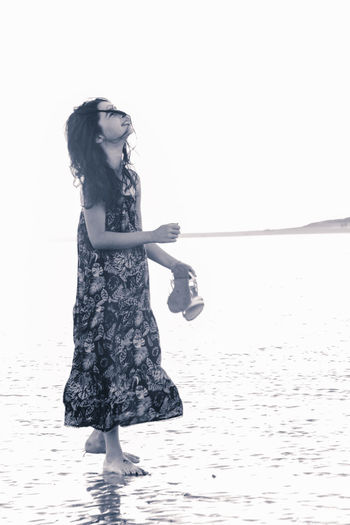 Side view of girl standing at beach against clear sky