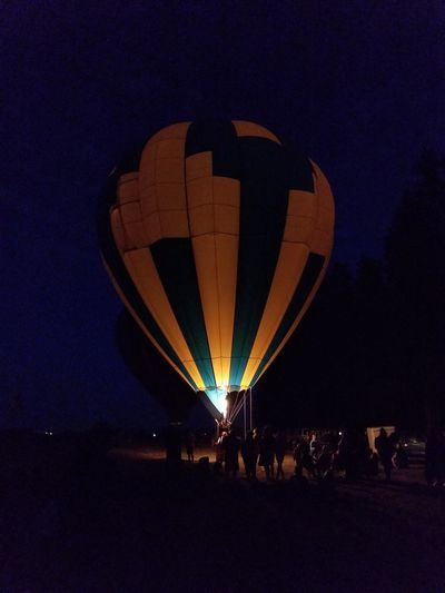 Hot Air Balloon Night Ballooning Festival Adventure Flame Full Length Sky People Transportation Illuminated Landscape Travel Destinations Outdoors Vacations Flying Nature Cityscape City Adult Astronomy