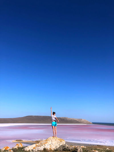 Woman standing on beach against clear blue sky