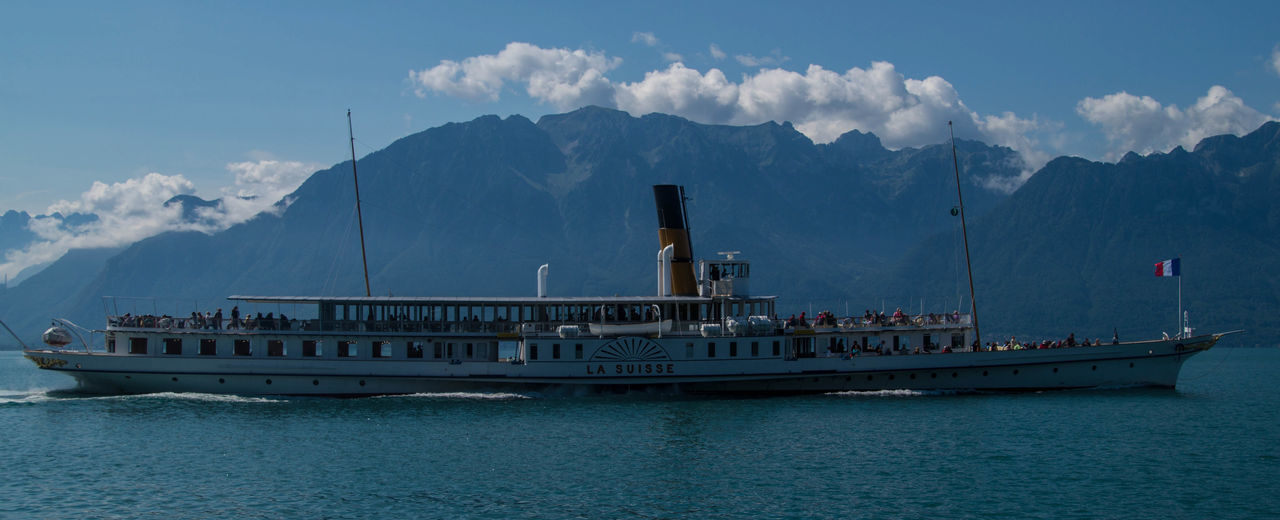 mountain, nautical vessel, transportation, sky, mode of transport, cloud - sky, day, flag, sea, nature, water, outdoors, scenics, cruise ship, mountain range, beauty in nature, ferry, architecture, no people