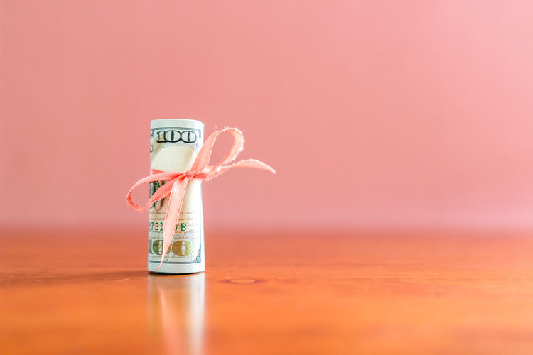 Concept of US dollar rolled and tied with ribbon on the wooden surface over pink background with copy space. Selective focus with shallow depth of field. Colored Background Copy Space Still Life Wrapped Work Wealth USA Tied Up Success Studio Shot Sign Savings Roll Ribbon Retirement Relief Prize Present Pink Color Paper Number Note Money Isolated Investment HUNDRED Gift Financial Finance Dollar Decoration Currency Concept Close-up Cash Business Bill Abundance Banking Banknote