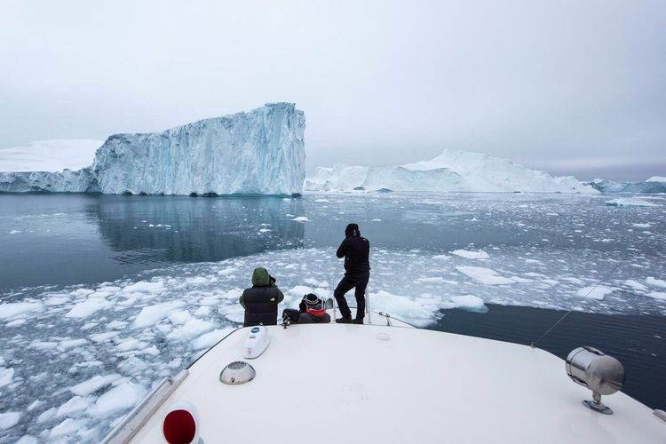Rear view of people photographing glaciers