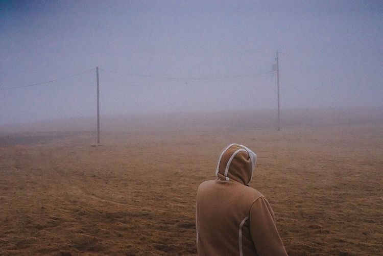 Rear view of woman in warm clothing standing on field during foggy weather