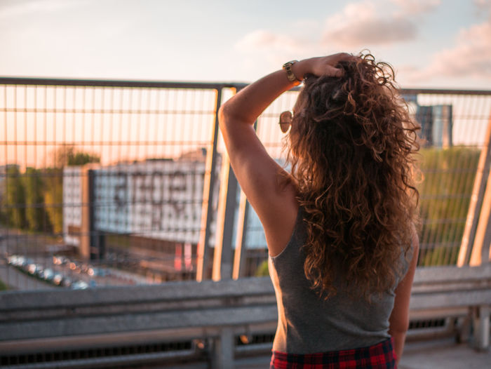 Rear view of woman with hand in hair standing against railing during sunset