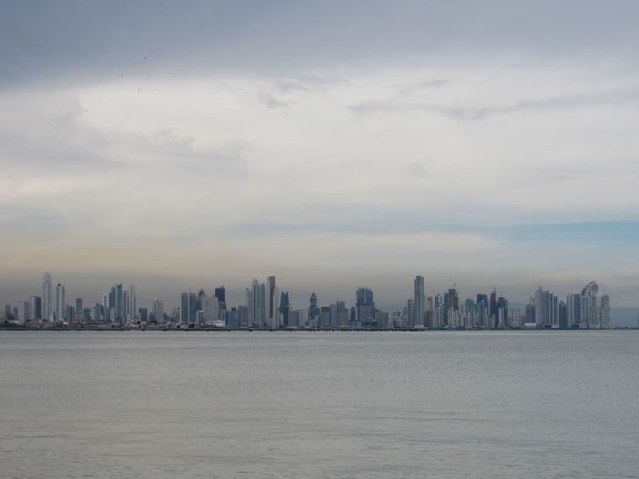 Sea and buildings in city against sky