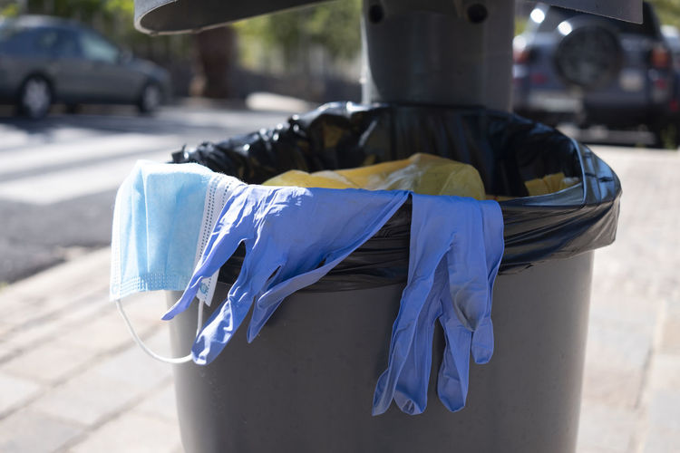 View of surgical glove and mask in dustbin outdoors