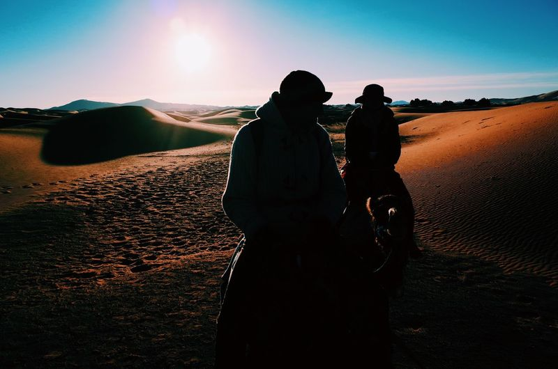 Silhouette men on camels at desert against sky