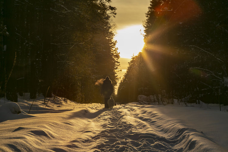 Woman walking on snow covered land against sky at sunset