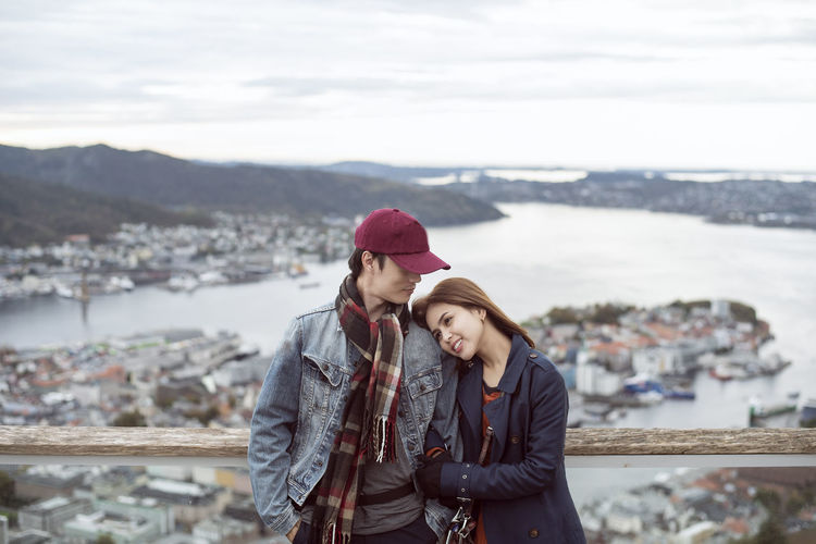 Couple standing on mountain against sky