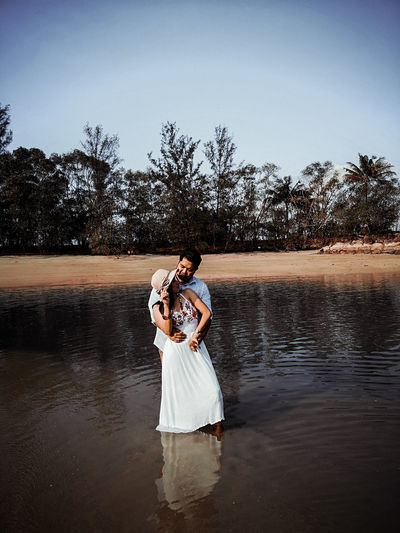 Couple romancing while standing on shore at beach