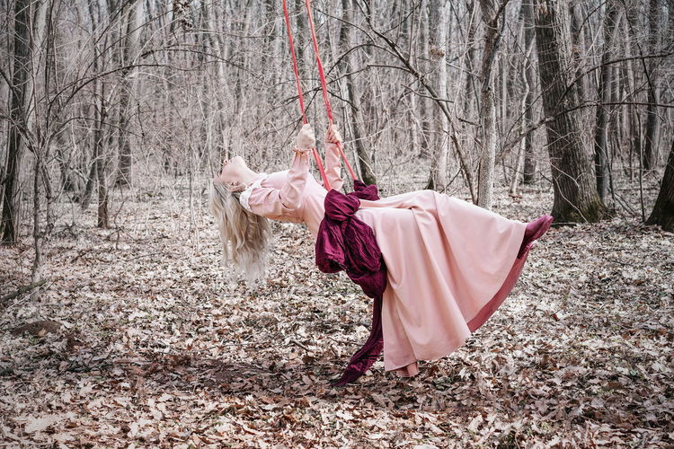 Woman swinging in swing by bare trees in forest