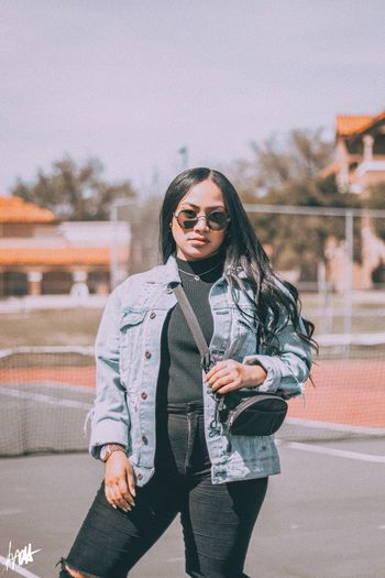 Young woman wearing sunglasses standing against sky