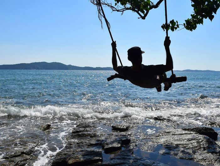 Silhouette man swinging on rope swing over sea against clear sky