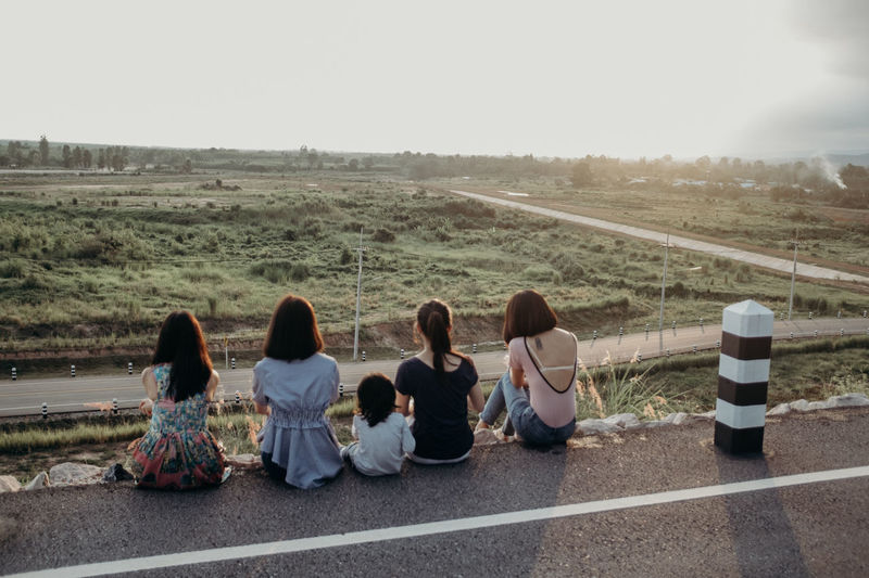 Rear view of people sitting on road
