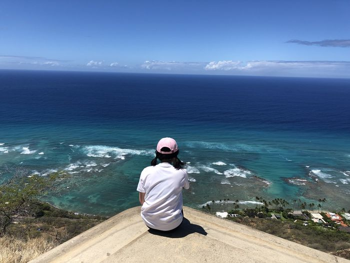 Rear view of woman looking at sea while sitting on observation point