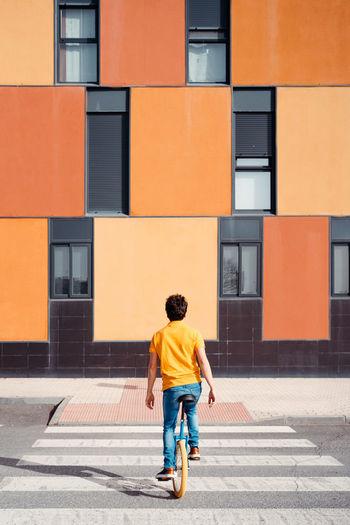 Full length rear view of man walking on street against building