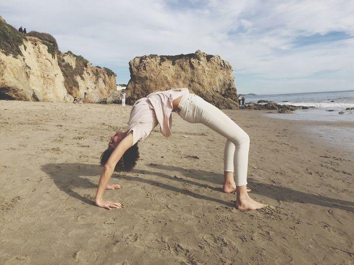 Woman Bending At Beach Against Sky