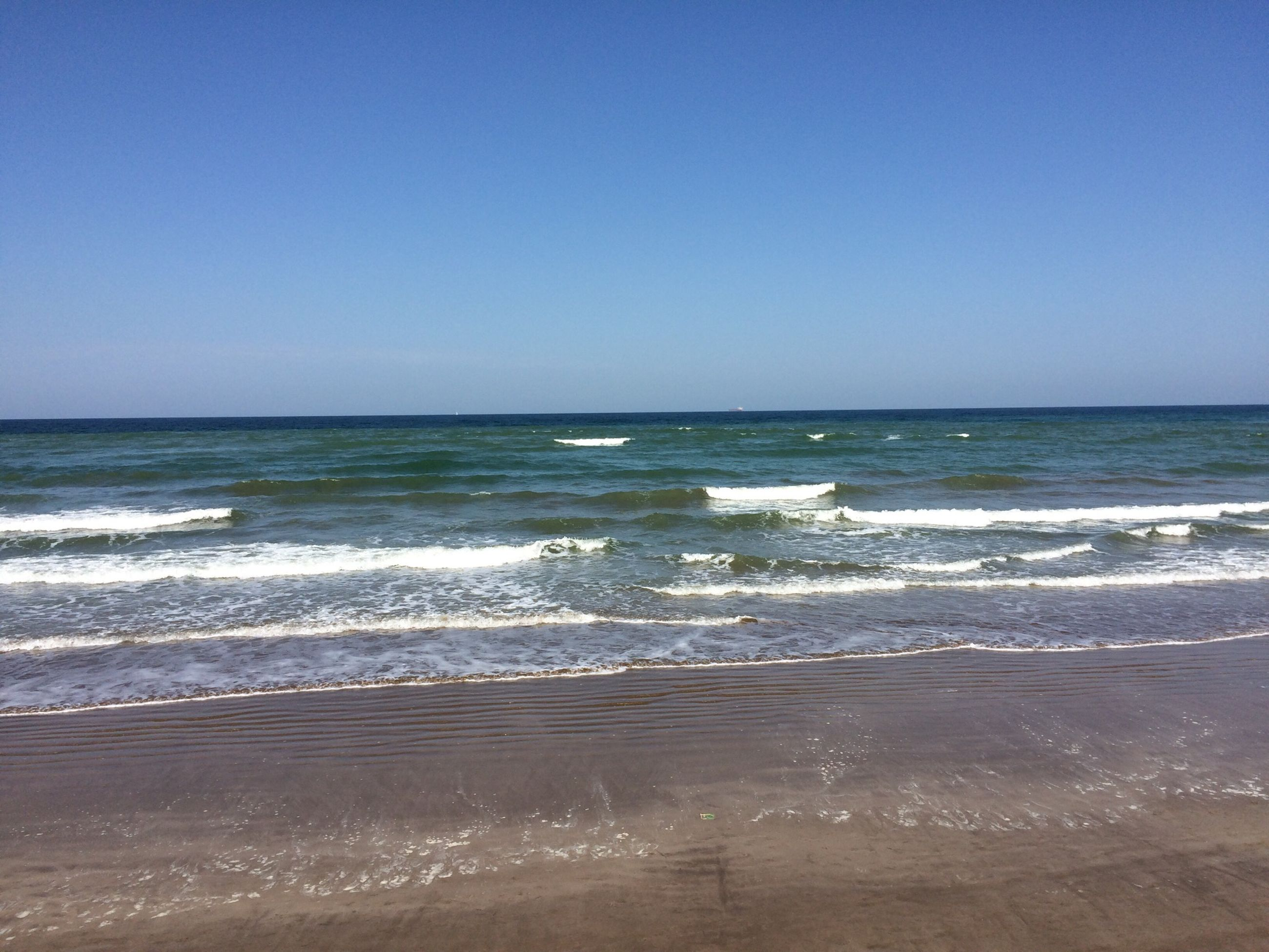 sea, horizon over water, water, clear sky, beach, copy space, shore, scenics, wave, tranquil scene, beauty in nature, blue, tranquility, sand, nature, surf, idyllic, seascape, day, outdoors