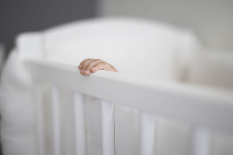 Cropped Hand Of Baby In White Crib At Home