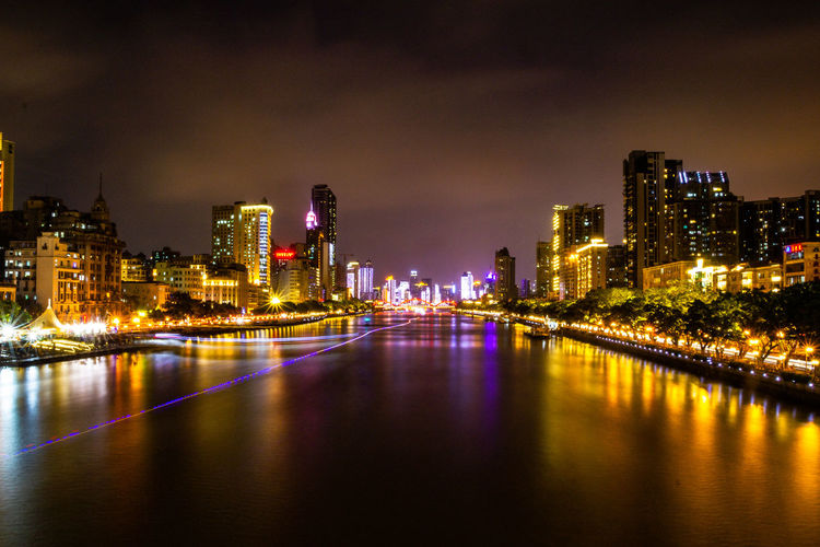 River amidst illuminated buildings against sky at night