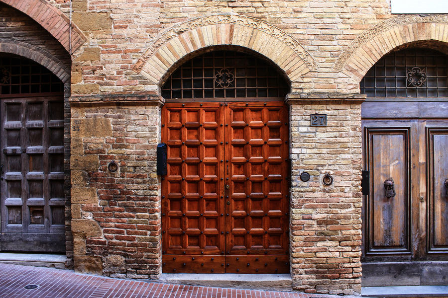 Art Is Everywhere Arch Door Architecture Built Structure Day Building Exterior Wood - Material Outdoors No People Close-up Streetphoto_color Emptiness Architecture Street Photograpy EyeEmNewHere Windows And Doors Travel Destinations San Gimignano Italy Lifestyles