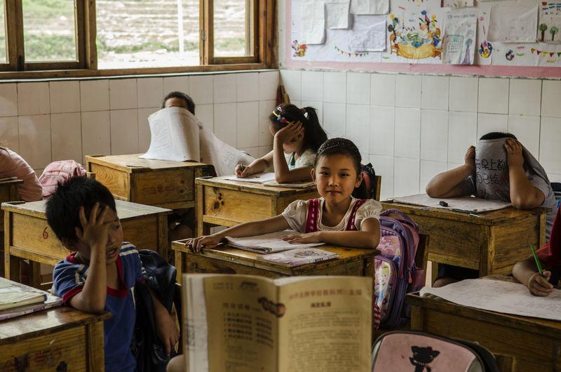 Children sitting on books in shelf