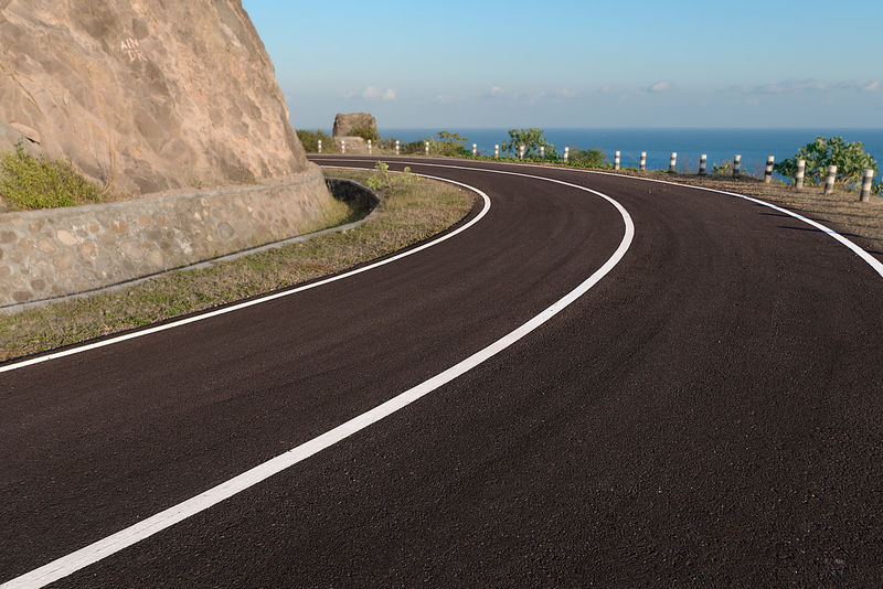 Asphalt coastal road going round cliff edge bend, with blue sea back drop. Beach Road Cliff Face Curve Road White Lines Asphalt Beauty In Nature Cliff Curve Day Nature No People Outdoors Road Road Lines Scenics Sky Tarmac The Way Forward Tranquil Scene Transportation