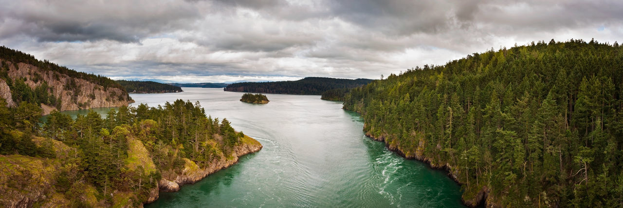 Deception Pass Panorama. Deception Pass is a strait separating Whidbey Island from Fidalgo Island, in the northwest part of the U.S. state of Washington. It connects Skagit Bay, part of Puget Sound, with the Strait of Juan de Fuca. A pair of bridges known collectively as Deception Pass Bridge cross Deception Pass, and the bridges are on the National Register of Historic Places. Beauty In Nature Clouds Coastline Current Deception Pass Destination Idyllic Island Landscape Majestic National Register Of Historic Places Nature No People Outdoors Outdoors Photograpghy  Pacific Northwest  Panorama Puget Sound Scenics Sea Shore Strait Tide Washington Water