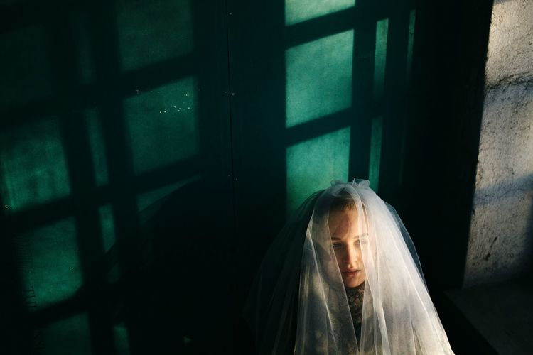 High angle view of depressed bride wearing veil by window
