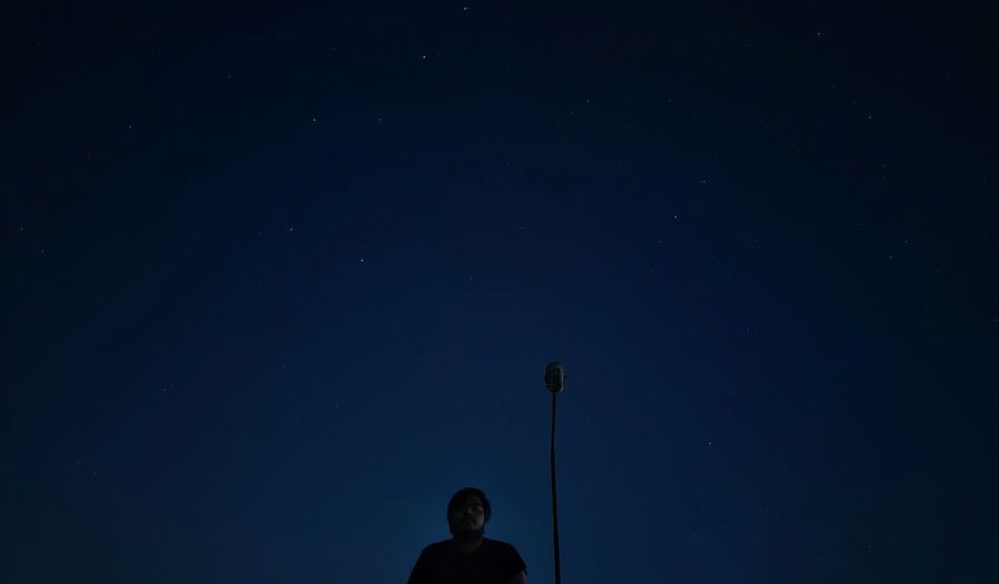 Low angle view of man standing against sky at night