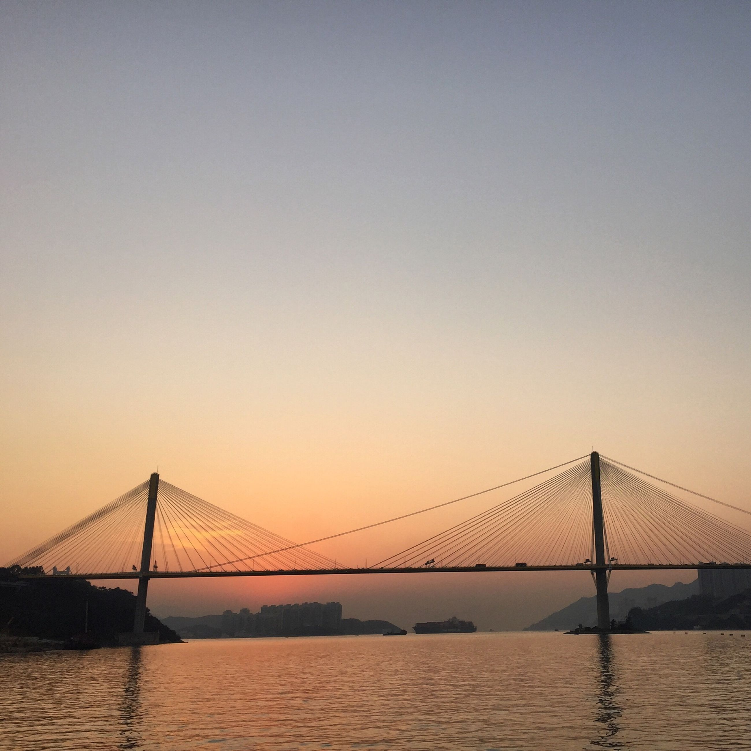 connection, bridge - man made structure, water, engineering, suspension bridge, built structure, bridge, architecture, sunset, waterfront, transportation, river, clear sky, travel destinations, sea, tranquility, silhouette, copy space, tranquil scene, long