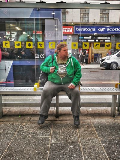 Full length of man sitting on bench in city