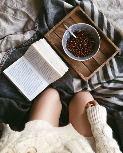 Midsection Of Woman With Book And Pomegranate Seeds On Bed At Home