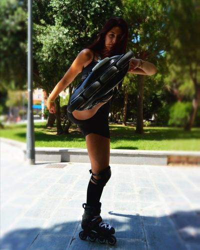 Portrait of young woman kicking while roller skating at park on sunny day