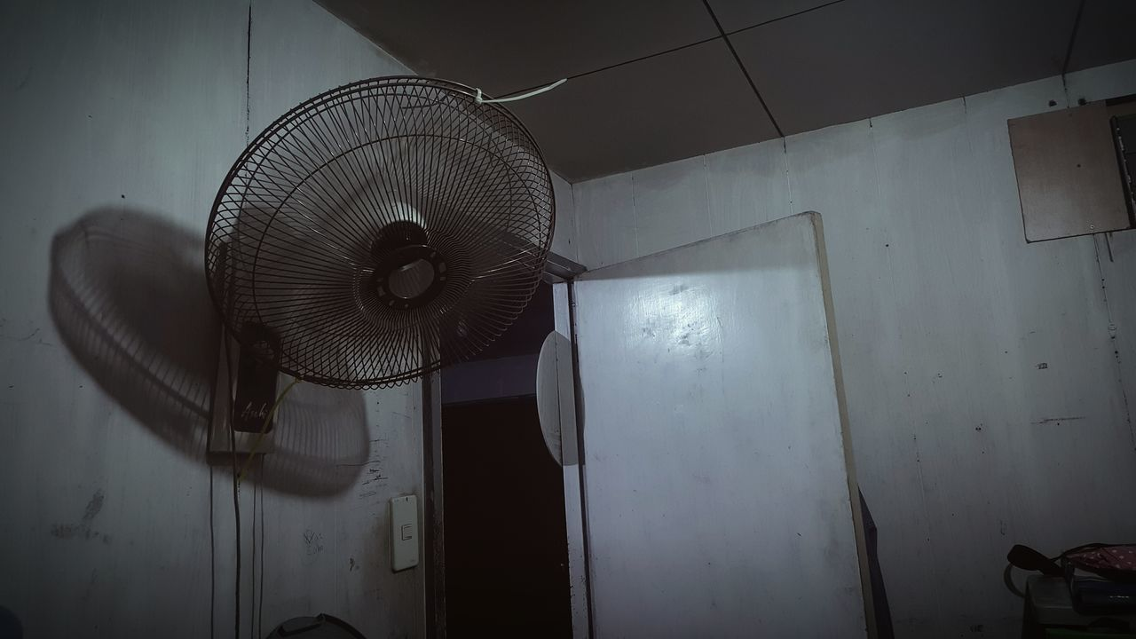fan, electric fan, indoors, no people, wall - building feature, technology, appliance, metal, electricity, low angle view, exhaust fan, architecture, ceiling, absence, lighting equipment, built structure, light bulb, household equipment, old, air duct