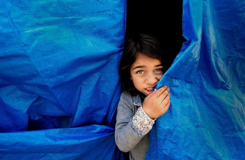 Close-up portrait of child hiding behind tarpaulin
