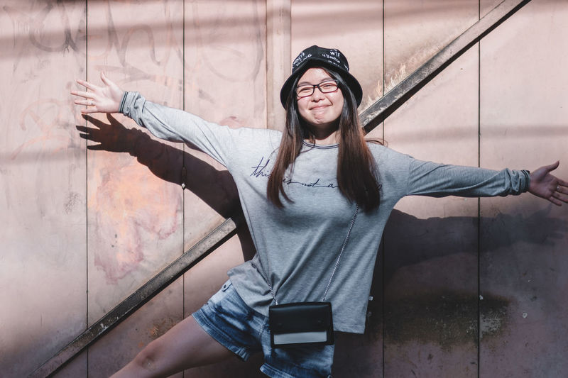 Front View Lifestyles One Person Real People Young Adult Young Women Glasses Casual Clothing Leisure Activity Standing Portrait Three Quarter Length Wall - Building Feature Smiling Looking At Camera Women Clothing Adult Human Arm Outdoors Hairstyle