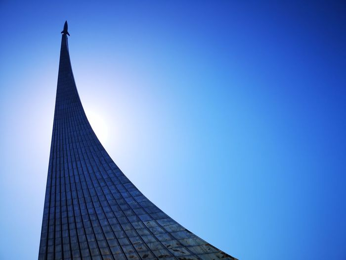 Low Angle View Of Modern Building With Rocket Against Blue Sky