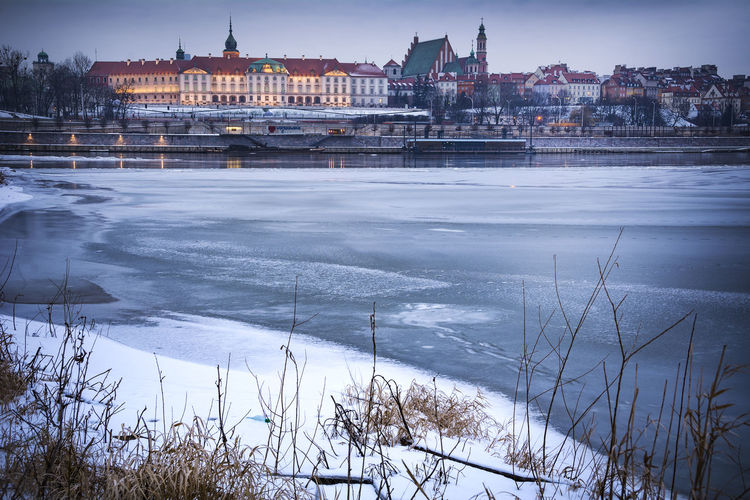 View of buildings by river during winter