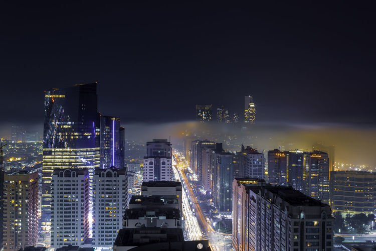High angle view of illuminated buildings against sky at night