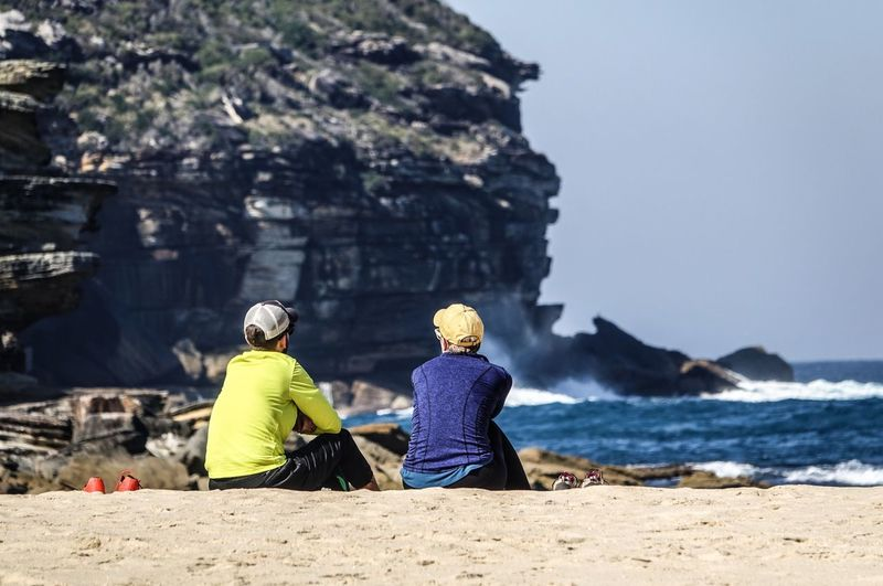 Rear view of people sitting on rock by sea