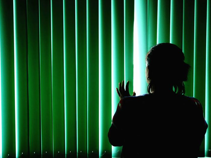 Rear view of woman looking through window blinds