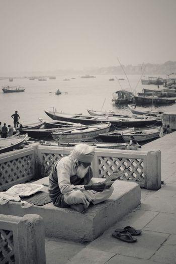 Man relaxing at harbor against sky