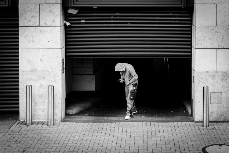 Sneaking Out Real People City Street Building Architecture One Person Lifestyles Sidewalk Casual Clothing Shutter person Man Düsseldorf Deutschland Monochrome Blackandwhite Black And White Streetphotography Urban City City Life Germany Canon Canonphotography